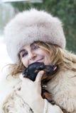 La jolie dame caressent son petit chien dans l'horaire d'hiver Image stock