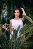 La jolie dame dans la jeune femme tropicale de la forêt A parmi les feuilles vertes fraîches La femelle avec du charme sur le ver Images libres de droits
