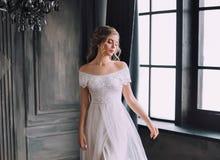 La jolie dame mystérieuse avec les cheveux bouclés blonds regarde vers le bas modestement, fille enchantée dans la longue robe bl photographie stock libre de droits
