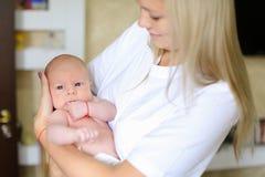 La jolie dame se tient dans des bras et pressé au coffre nouveau-né, étreignant Photos libres de droits