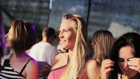 La jolie femelle blonde avec le dessus rose danse lentement près de l'autre fille mignonne de brune banque de vidéos