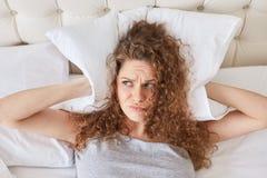 La jolie femelle de mécontentement avec les oreilles bouclées de couvertures avec l'oreiller, mensonges dans le lit, a l'insomnie images libres de droits