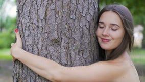 La jolie femme étreint un arbre, sent l'unité avec la nature, amour de la vie, unité extérieure banque de vidéos