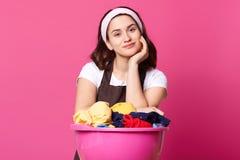 La jolie femme au foyer de jeune femme avec le bassin rose complètement des choses lavées propres, porte la bande de cheveux, T photo stock