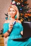 La jolie femme avec l'ordinateur portable et les achats de carte de crédit se présente près du ch Photographie stock