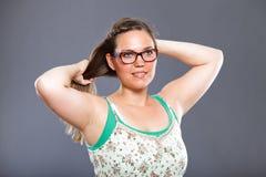 La jolie femme avec les verres de port de longs cheveux bruns et la fleur s'habillent Photographie stock libre de droits