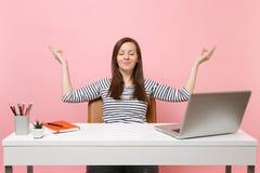 La jolie femme avec la méditation fermée de yeux a répandu des mains dans la pose de yoga pour s'asseoir après travail au bureau  image libre de droits