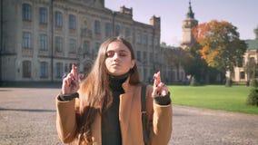 La jolie femme caucasienne se tient avec ses doigts a croisé et démonstration souhaitant le geste luxuriant, fond urbain banque de vidéos