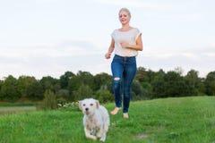 La jolie femme court avec un chien hybride de terrier dehors Images stock