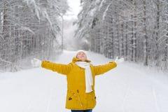 La jolie femme dans la forêt d'hiver se réjouit dans la neige Photographie stock