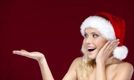 La jolie femme dans le capuchon de Noël fait des gestes la paume vers le haut photos stock
