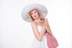 La jolie femme dans le chapeau élégant tenant le blanc rouge a dépouillé le sac Femme de sourire de mode Images stock