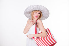 La jolie femme dans le chapeau élégant tenant le blanc rouge a dépouillé le sac Femme de sourire de mode Image libre de droits