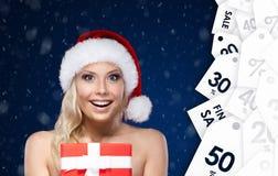 La jolie femme dans le chapeau de Noël remet le présent enveloppé avec le papier rouge image libre de droits
