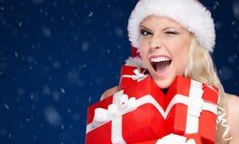 La jolie femme dans le chapeau de Noël tient un ensemble de présents image stock