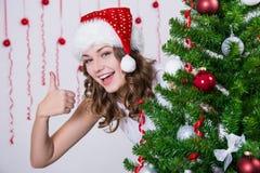 La jolie femme dans le chapeau de Santa manie maladroitement vers le haut de l'arbre de Noël proche Photo libre de droits