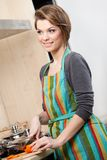 La jolie femme dans le tablier rayé fait cuire des légumes Photo stock