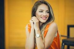 La jolie femme de mode porte des vêtements d'automne au-dessus de fond en bois jaune Photographie stock libre de droits