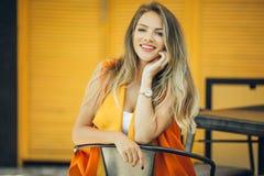 La jolie femme de mode porte les vêtements vibrants d'automne au-dessus du fond en bois jaune Image libre de droits
