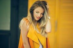 La jolie femme de mode porte les vêtements vibrants d'automne au-dessus du fond en bois jaune Photos stock