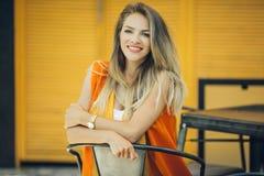 La jolie femme de mode porte les vêtements vibrants d'automne au-dessus du fond en bois jaune Image stock
