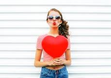 La jolie femme de portrait faisant le baiser d'air avec le rouge monte en ballon la forme de coeur au-dessus du blanc Photo stock