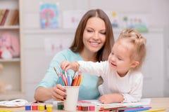 La jolie femme enseigne son enfant à dessiner Photo libre de droits