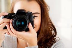 La jolie femme est une photographe de proffessional avec l'appareil-photo de dslr photo stock