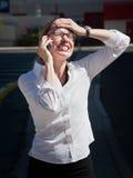La jolie femme exaspérée parle sur le téléphone portable Photos stock