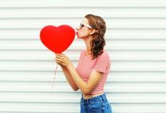 La jolie femme faisant le baiser d'air avec le rouge monte en ballon la forme de coeur au-dessus du blanc Photographie stock libre de droits