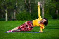 La jolie femme faisant le yoga s'exerce en parc photos stock