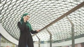 La jolie femme musulmane dans un hijab avec un sac à dos va au centre commercial et aux entretiens au téléphone clips vidéos