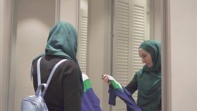 La jolie femme musulmane dans un hijab et avec un sac à dos essaye des vêtements devant un miroir dedans banque de vidéos