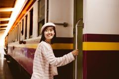 La jolie femme obtient dans le train à la station de train pour la maison arrière allante à l'aide du train public La belle femme photographie stock libre de droits