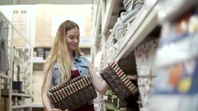 La jolie femme prend d'une étagère dans un kit de supermarché de boîtes clips vidéos