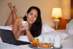 La jolie femme prend le petit déjeuner dans un lit d'hôtel photo libre de droits