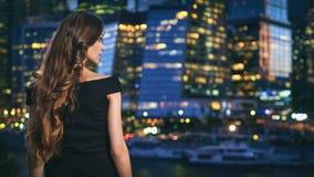 La jolie femme regarde la ville de nuit Photographie stock