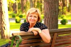 La jolie femme s'assied sur un banc et un sourire Photos stock