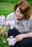 La jolie femme s'occupe derrière des usines dans le jardin photo stock