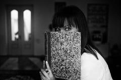 La jolie femme se cache derrière le livre se reposant à son salon photo stock