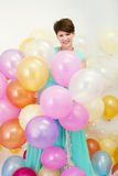 La jolie femme tient le grand groupe de ballons colorés Image stock