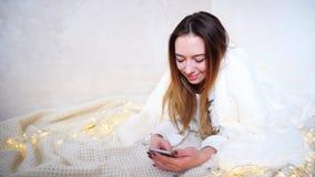La jolie fille écrit le message de félicitations au téléphone à l'aimé Photo stock