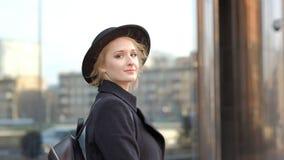 La jolie fille étroite dans le manteau noir tient le chapeau écoutant la musique avec des écouteurs contre le mouvement lent de b banque de vidéos