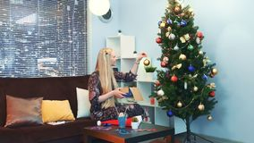 La jolie fille accroche des jouets sur l'arbre de Noël avec des gratte-ciel sur le fond banque de vidéos