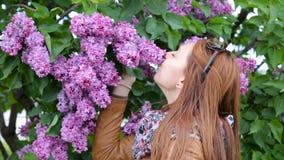 La jolie fille apprécie le parfum du lilas Respire le parfum des fleurs banque de vidéos