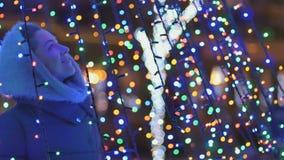 La jolie fille apprécie une illumination lumineuse de Noël clips vidéos