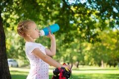 La jolie fille avec la bicyclette boit l'eau en parc d'été Photo stock
