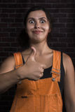 La jolie fille avec l'expression du visage drôle montrant des pouces lèvent le signe Image stock