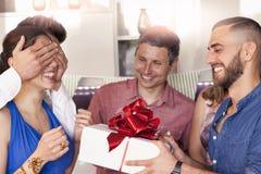 La jolie fille avec le gâteau d'anniversaire recevant le cadeau du sien frien Photographie stock libre de droits