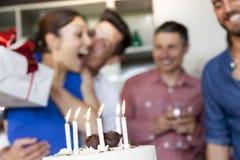 La jolie fille avec le gâteau d'anniversaire recevant le cadeau du sien frien Photos stock